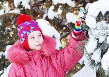 Little girl touches snowy pine tree branches in the park Stock Images