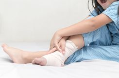 Little girl touching ankle with elastic bandage. Broken leg, painful and health care concept Stock Photo