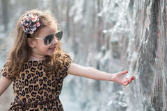 Little girl touching hand waterfall. Little girl in a leopard dress touching hand waterfall royalty free stock photography