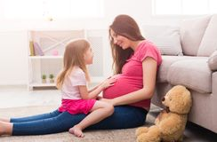 Little girl touching her pregnant mother belly Royalty Free Stock Photography