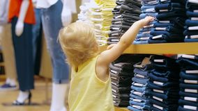 Little girl touching jeans lying on shelves in clothing store stock video