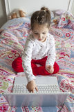 Little girl touching the pc screen while she is playing Stock Image