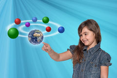 Little girl is touching the Planet Earth. Smiling little girl is touching the Planet Earth and showing another color balls. All is on on the blue gradient royalty free stock images
