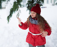 Little girl touching snow on fir-tree branch Royalty Free Stock Photos