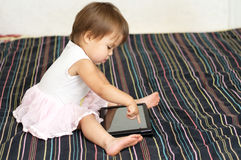 Little girl touching  a Tablet PC touch screen with finger cute Royalty Free Stock Images