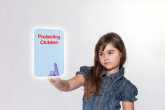 Little girl with is touching a transparent rectangle. Little girl with a serious expression is touching a blue transparent rectangle with inscription Royalty Free Stock Photo