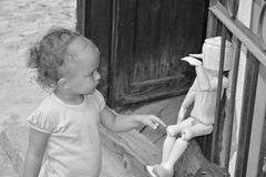 Little girl touching wooden puppet Stock Photos
