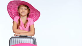 Little girl tourist with travel suitcase showing thumb up sign. Little girl tourist in wide brimmed summer hat with travel suitcase and a ring on it, showing stock footage