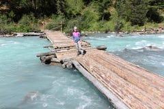 Little girl tourist walking along a wooden bridge across a river stock photography