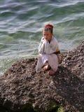 Little girl in towel near sea on rock stock photos