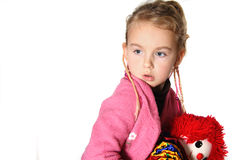 Little girl with toy. A 5 year old posing and holding a toy, while loocking down Stock Photos