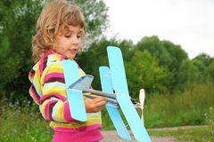 Little girl with toy airplane in hands outdoor Stock Photos