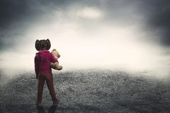 Little girl with toy bear in the darkness Royalty Free Stock Images
