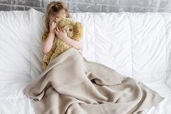 A little girl and a toy bear. Are sitting on a white sofa. She is playing beige knitted blanket royalty free stock photos