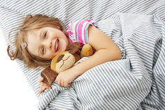 Little girl with toy in the bed. And white background Stock Photo