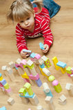 Little girl with toy blocks. Little girl lying on the floor, playing with wooden toy blocks Royalty Free Stock Image