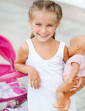 Little girl with  toy carriage Royalty Free Stock Photos