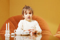 Little girl with toy dishware Royalty Free Stock Photo