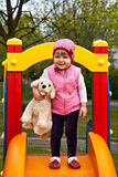 Little girl with toy dog at playground Stock Photos