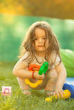 Little girl with toy in hands. Stock Images