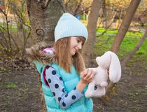 Little girl with a toy hare Stock Photo