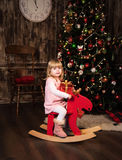 Little girl on a toy horse Stock Images
