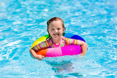 Little girl with toy ring in swimming pool. Happy little girl playing with colorful inflatable ring in outdoor swimming pool on hot summer day. Kids learn to Stock Image
