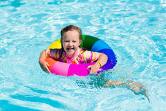 Little girl with toy ring in swimming pool. Happy little girl playing with colorful inflatable ring in outdoor swimming pool on hot summer day. Kids learn to Royalty Free Stock Photography