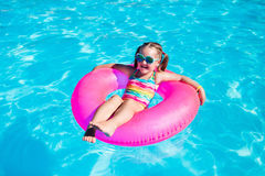 Little girl with toy ring in swimming pool Stock Photo