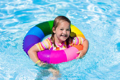 Little girl with toy ring in swimming pool. Happy little girl playing with colorful inflatable ring in outdoor swimming pool on hot summer day. Kids learn to Stock Images