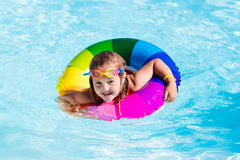 Little girl with toy ring in swimming pool. Happy little girl playing with colorful inflatable ring in outdoor swimming pool on hot summer day. Kids learn to Stock Photos