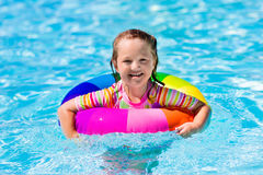Little girl with toy ring in swimming pool. Happy little girl playing with colorful inflatable ring in outdoor swimming pool on hot summer day. Kids learn to Stock Photography
