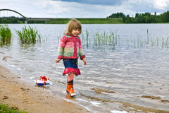 Little girl with a toy ship Stock Image