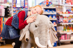 Little girl in toy store cuddling with stuffed animal Royalty Free Stock Images