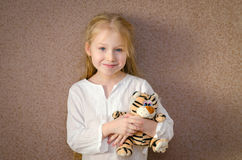 Little girl with toy tiger Royalty Free Stock Photo