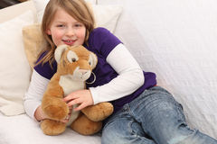 Little girl with toy tiger on sofa Royalty Free Stock Image