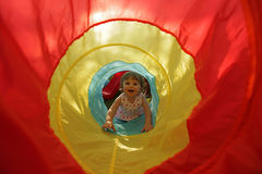 Little girl in a toy tunnel Royalty Free Stock Images