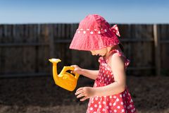 Little girl with a toy watering-can Stock Image