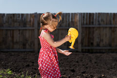 Little girl with a toy watering-can Stock Photography