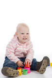 Little girl  with toys. The little girl sitting on the floor and playing with toys Stock Image