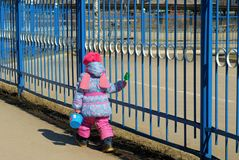 Little girl with toys going along the street. Near an iron fence in the sunny day Royalty Free Stock Photos