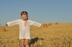 A little girl in a traditional chemise standing barefoot in a harvested field with ears in her hand Stock Image