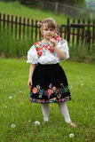 Little girl in traditional costume with flowers Stock Photos