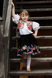 Little girl in traditional costume on the stairs Royalty Free Stock Photo