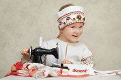 Little girl in the traditional russian shirt and kokoshnik at the process of sewing