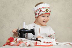 Little girl in the traditional russian shirt and kokoshnik at the process of sewing.  Royalty Free Stock Images