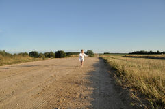 A little girl in a traditional slavic ornamented сhemise running barefoot in along a country road Royalty Free Stock Photo
