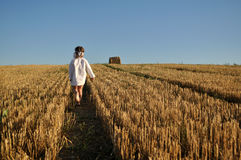 A little girl in a traditional slavic ornamented сhemise running barefoot in a harvested field Stock Images