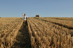 A little girl in a traditional slavic ornamented сhemise running barefoot in a harvested field Royalty Free Stock Photo