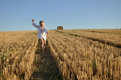 A little girl in a traditional slavic ornamented сhemise running barefoot in a harvested field Royalty Free Stock Photography